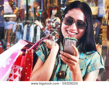 Asian Woman Carrying Shopping Bags And Texting Massage