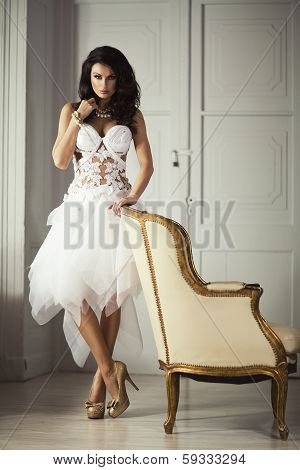Beautiful Adult Woman With Fashion Hairstyle And White Armchair Poses