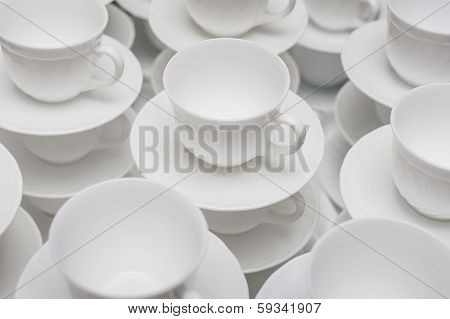 Cups set on saucers in stacks.