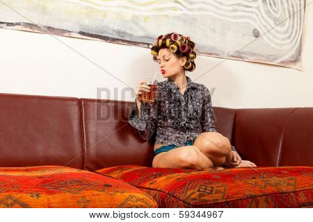 sexy girl with drink on the couch in the living room
