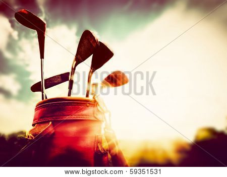 Golf equipment in vintage, retro style. Professional clubs in a leather baggage at sunset