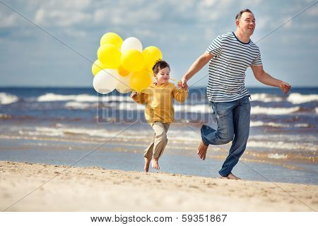 Family with yellow balloons playing on the beach
