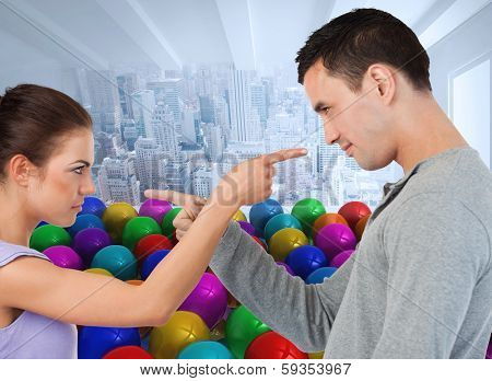 Young couple pointing at each other against many colourful balloons in room with city scene