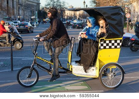 PARIS, FRANCE - JANUARY 6, 2012: Tourists driving in bicycle taxi and taking photos.