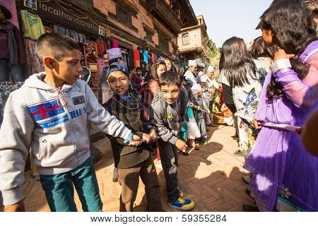 BHAKTAPUR, NEPAL - DEC 20: Unidentified children during Birthday celebration head of family - 77 years 7 months 7 days 7 hours old, like rebirth according to Newar, Dec 20, 2013 in Bhaktapur, Nepal.