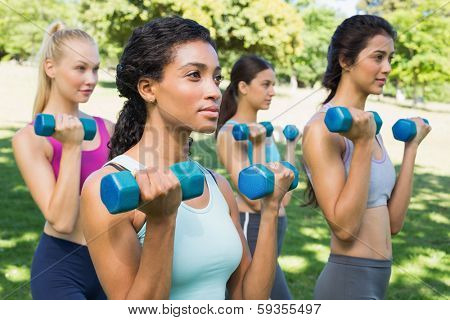 Group of multiethnic sporty women lifting dumbbells in park