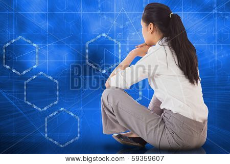 Businesswoman sitting cross legged against abstract technology background