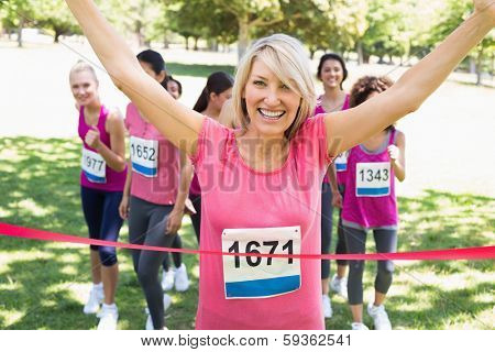 Portrait of happy female winner of breast cancer marathon race at park