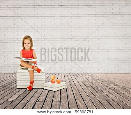 little girl reading a book on a room with white bricks wall and wood floor