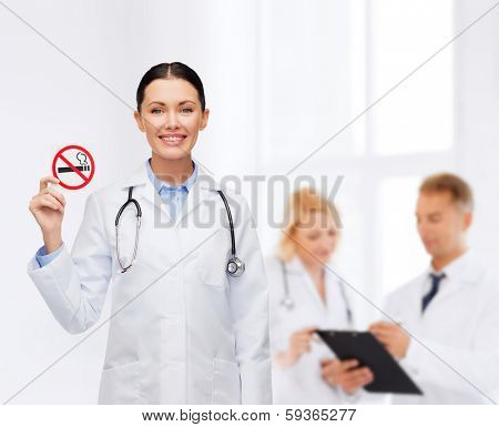 healthcare and medicine concept - smiling female doctor with stethoscope holding no smoking sign