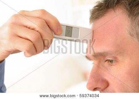 Man attempting to measure body temperature with thermometer on forehead