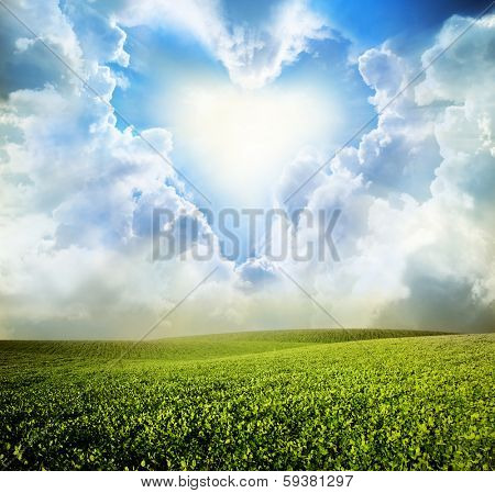 Green meadow under blue sky with heart clouds