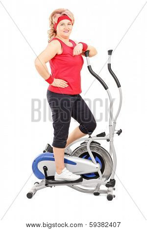 Mature lady posing on a cross trainer machine isolated on white background