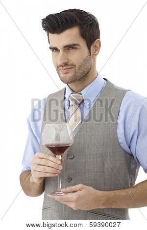 Portrait of young man holding glass of wine, looking away.