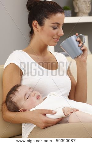 Young mother drinking tea in peace while baby sleeping in her arms.