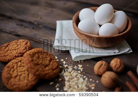 Several eggs in bowl with walnuts and bisquits near by