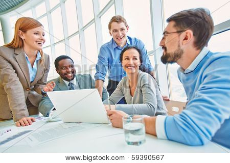 Group of business partners looking at their colleague while he sharing his ideas at meeting