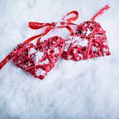 Image of two beautiful romantic vintage red hearts tied together with a ribbon on a white snow background. Love and st. Valentines day concept.