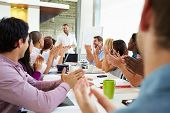 image of applause  - Businessman Addressing Meeting Around Boardroom Table - JPG