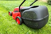 image of grass-cutter  - new lawnmower on green grass in cloudy day