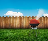 stock photo of kettling  - a kettle barbecue grill on a backyard - JPG