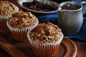 Freshly baked honey raisin muffins in rustic setting.  Vintage pewter dishes with ingredients in bac