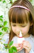 picture of nasal catarrh  - Little girl spraying medicine in nose nose drops nose spray - JPG