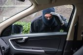 stock photo of theft  - A burglar in action to rob something out of a car - JPG