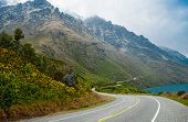 foto of long winding road  - A two lane road passes beside a lake and winds along the base of a misty mountain south of Queenstown on New Zealand - JPG