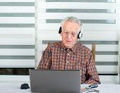 stock photo of older men  - Older man using laptop for internet communication - JPG