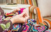pic of quilt  - Hands of senior woman knitting a vintage wool quilt with colorful patches