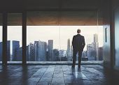 stock photo of skyscrapers  - Young business man standing on a balcony and looking at city - JPG