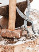 foto of tong  - blacksmith anvil tongs and hammer in old country smithy in winter - JPG