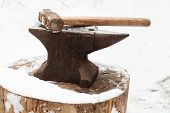 image of anvil  - anvil with hammer in old abandoned village smithy in winter - JPG