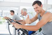 pic of exercise bike  - Portrait of happy man on exercise bike gesturing thumbs up at gym - JPG