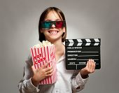 little girl wearing 3D glasses and eating popcorn