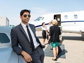 Confident businessman leaning on car with airhostess and pilot greeting business people against priv