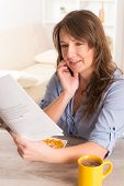 Beautiful young woman eating cornflakes and reading newspaper at home