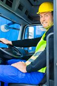 image of heavy equipment operator  - driver driving with the truck over building or construction site - JPG