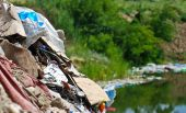 stock photo of non-biodegradable  - Discarded industrial waste being dumped nead water - JPG