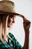 stock photo of redneck  - Beautiful young country girl woman wearing a stylish cowboy hat - JPG
