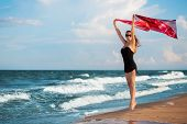image of leggy  - Attractive leggy woman with pink pareo posing near the sea - JPG