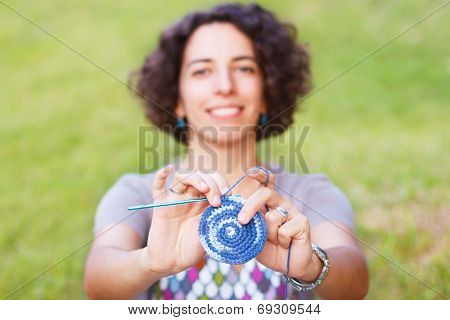 Happy Smiling Woman Making Crochet Potholder Outdoors