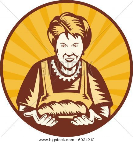old woman presenting a freshly baked loaf of bread