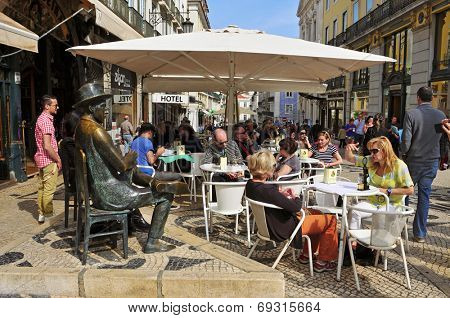 LISBON, PORTUGAL - MARCH 17: The crowded terrace of Cafe A Brasileira with the Statue of Fernando Pessoa on March 17, 2014 in Lisbon, Portugal. This statue and the cafe are visited for many tourists