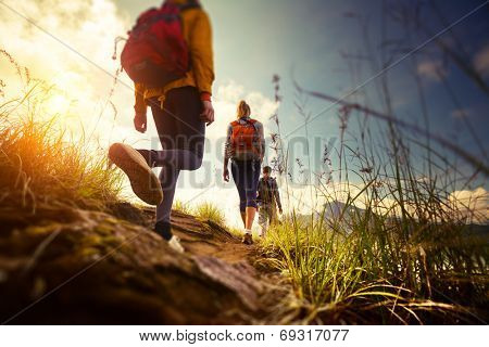 Group of hikers walking in mountains. Edges of the image are blurred