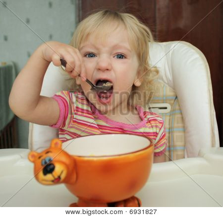 The little girl she eats with a spoon