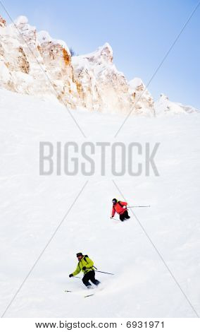 Two Skiers Going Downhill In Powder Snow