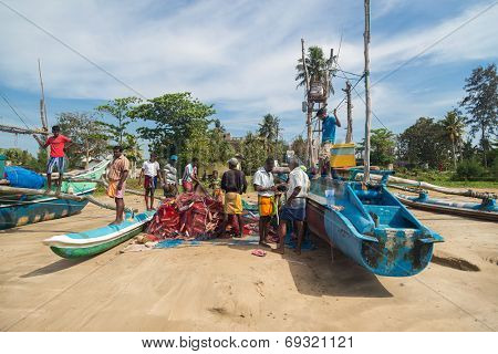 WELIGAMA, SRI LANKA - MARCH 7, 2014: Fishermen preparing fishing nets. Tourism and fishing are two main business in this town.