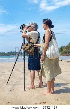 WELIGAMA, SRI LANKA - MARCH 7, 2014: Japanese tourists stand on sandy beach and take photos with old film camera. Tourism and fishing are two main business in this town.